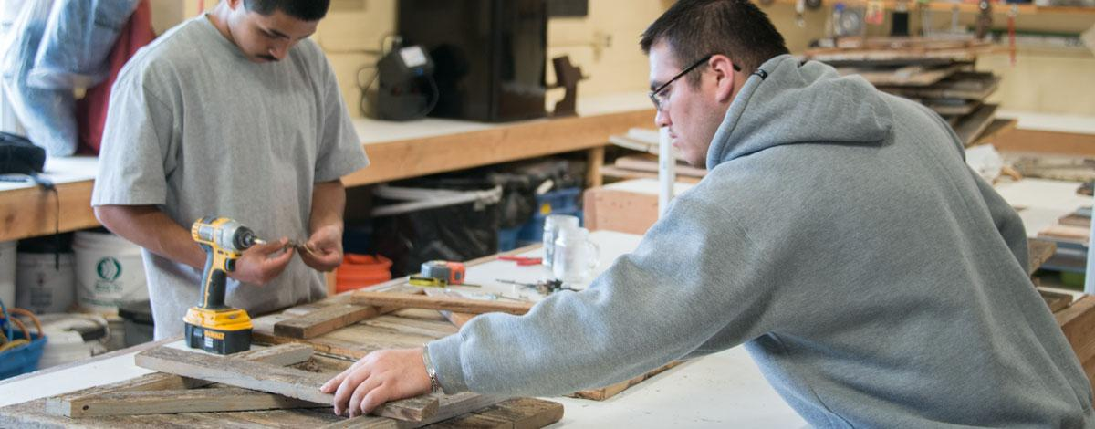 Students with wooden doors on work table